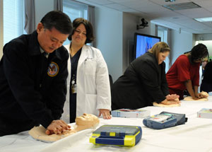 Secretary of Veterans Affairs Eric K. Shinseki (left) practices CPR compressions during Resuscitation Education Initiative (REdI) training at the VA Central Office